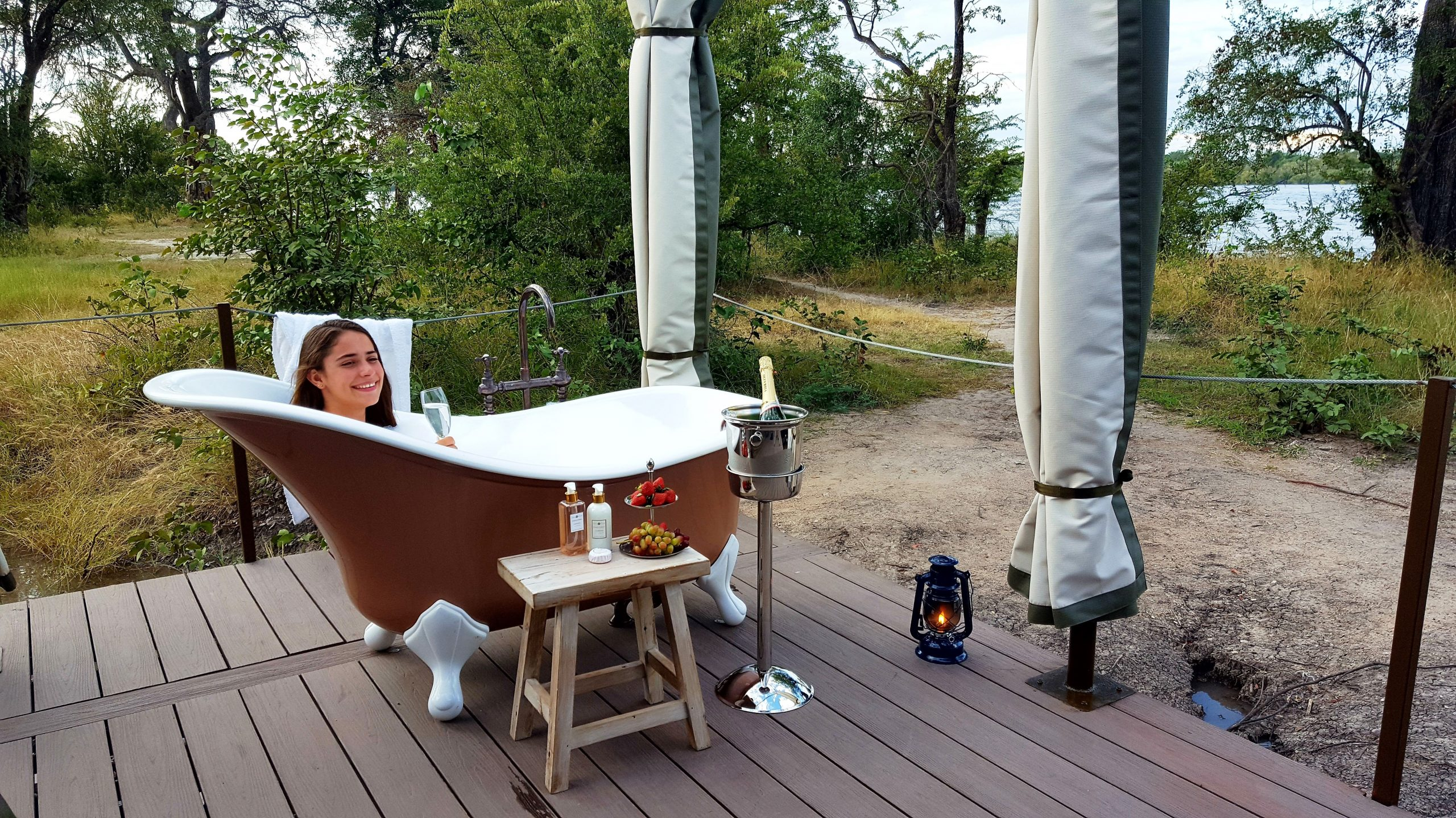 girl drinking champagne in outdoor bubble bath